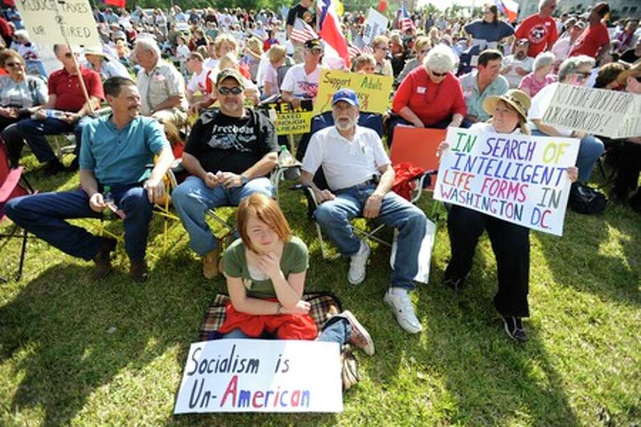 Autumn White, center, and from right, Sylvia Rose, and her husband Russel, gather with hundreds of people in a field across the street from the US Postal  Office on Walden Road to  participate in the SETX TEA Party on Wednesday. Valentino Mauricio/The Enterprise