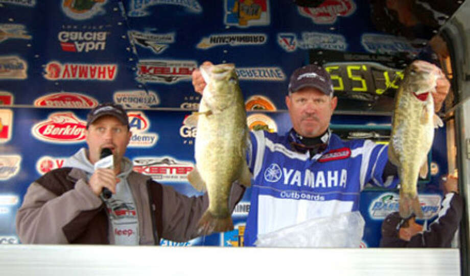 Brian Branum holds up two of the winning catch he and Bill Rogers accomplished to win Bass Champs with 22.70 lbs