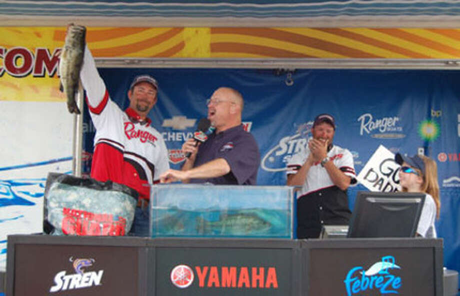 Russell Cecil holds up the bass that ultimately put his weight at the top for a 1st place win.  Scotty Villines clapps for his comrad, being bumped to 2nd place.
