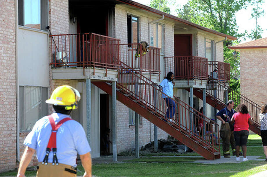 Mary Coleman descends a flight of stairs after a fire destroyed her granddaughter's apartment in Beaumont's south end on Tuesday. No injuries were reported. Guiseppe Barranco/The Enterprise