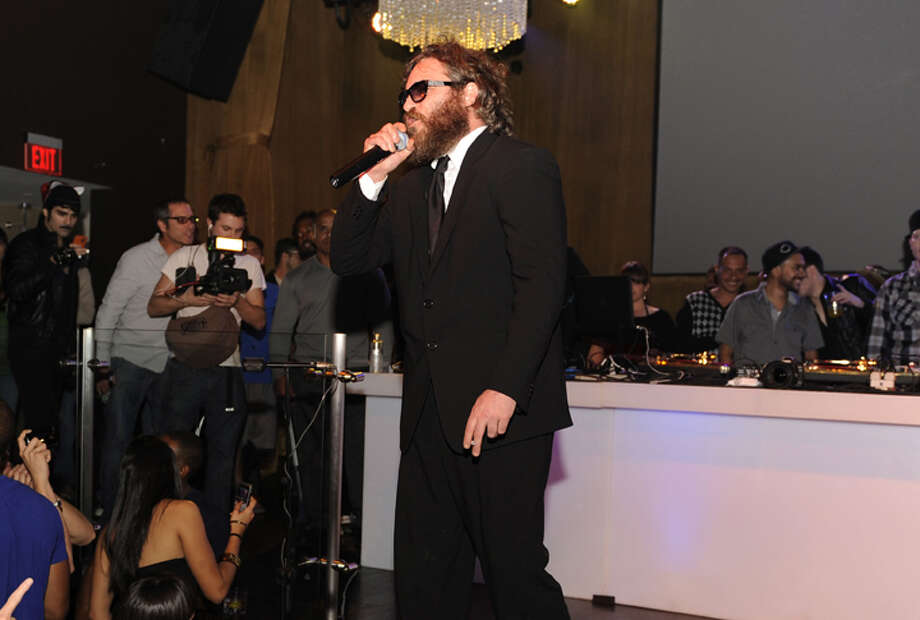 Joaquin Phoenix performs at the LIV nightclub at the Fountainbleau Hotel in Miami Beach, Fla., early Thursday, March 12, 2009 for a Belvedere 1X Party. Phoenix jumped off the stage during the short performance and confronted an audience member who was heckling him. Security guards dragged him back on stage and escorted Phoenix away. (AP Photo/Seth Browarnik) ** MAGS OUT, NO SALES ** / BROWS