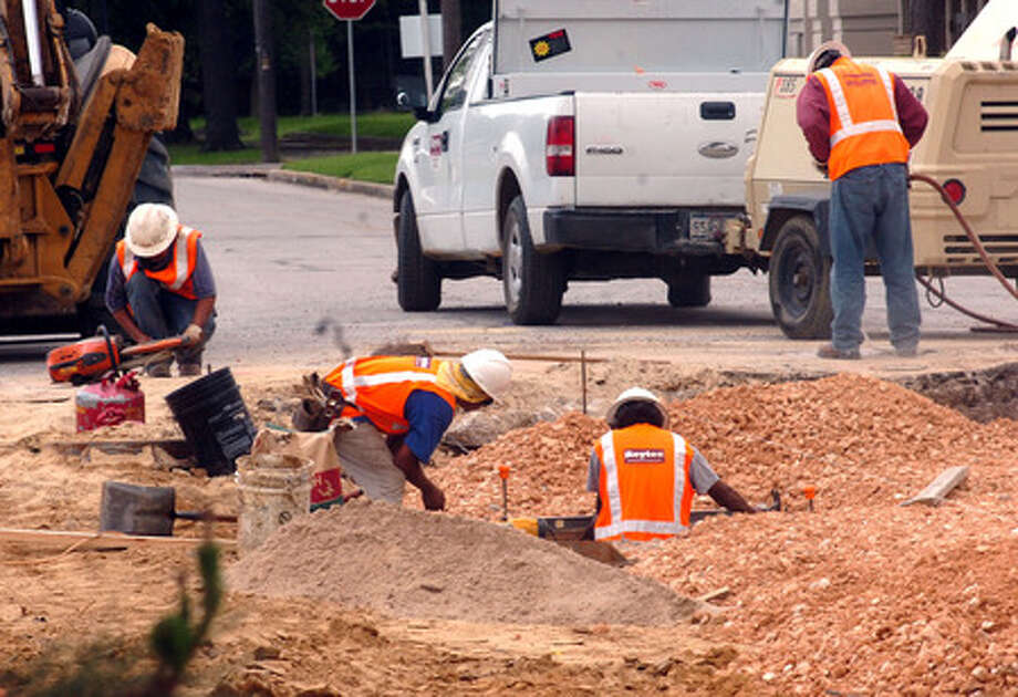 A construction crew works on te Calder project Monday afternoon at the intersection with Forrest Street in Beaumont. Pete Churton/The Enterprise
