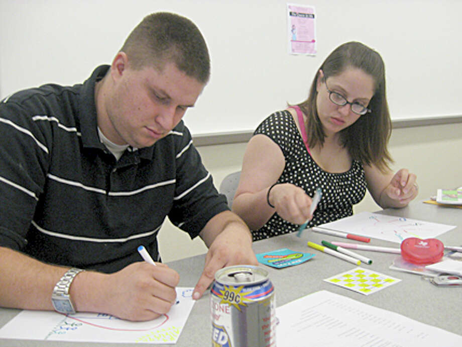 Justin Kelley, left, and his fianc?e Crystal Beukema draw pictures to reflect their definition of marriage. The couple was one of four couples to attend a Twogether in Texas marriage workshop Saturday. Emily Guevara/The Enterprise