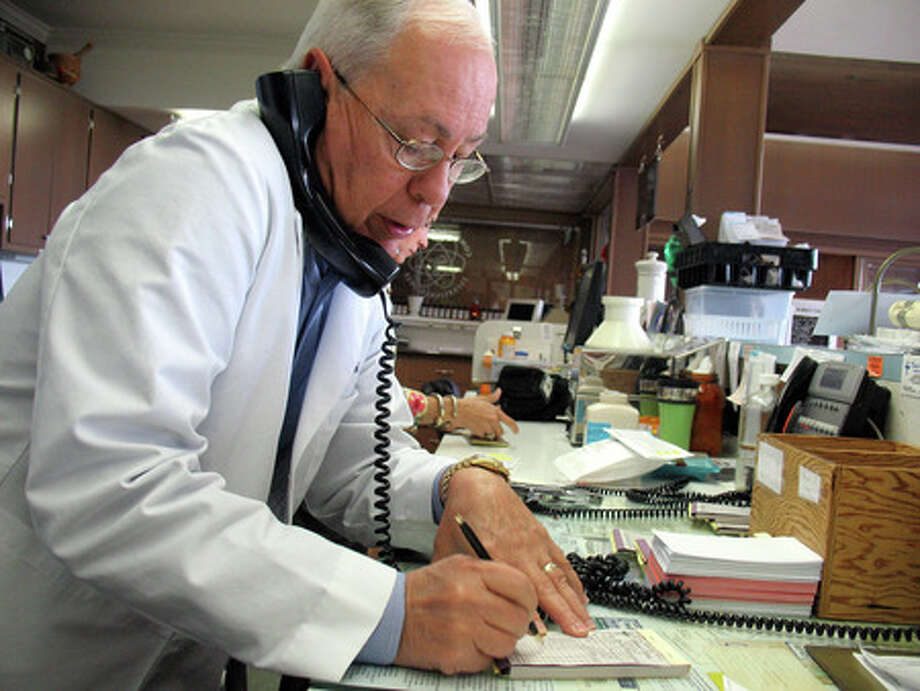 Local pharmacist Johnny Lovoi takes a phone call for a prescription at Lovoi and Sons Pharmacy in Beaumont. Lovoi, 70, has been part of the family business for more than 40 years. Amy Collins/The Enterprise