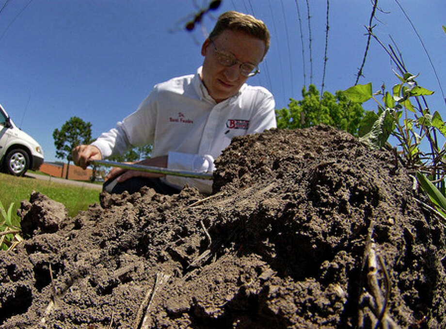 Bart Foster, a Ph.D. Entomologist with Bill Clark Pest Control, examines a large fire ant mound near the side of the road as one of the the ants begins to crawl over the camera lens.  Dave Ryan/The Enterprise