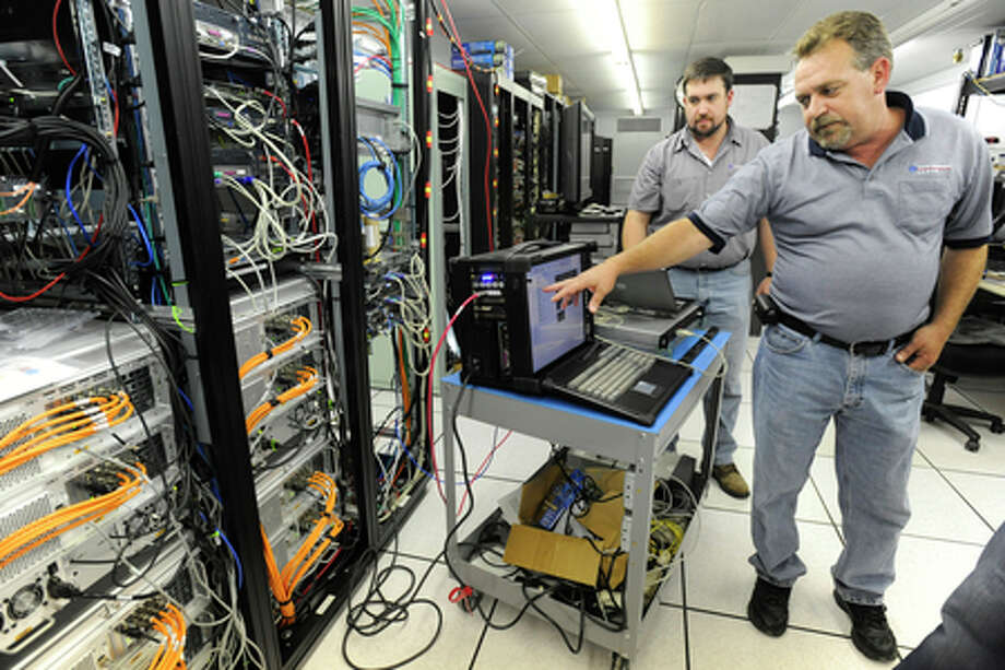 Time Warner Cable technicians, Keith Gesser, right, and Kevin Worlow work on a Video On Demand analyzer at a head end facility in Nederland on Friday.  Valentino Mauricio/The Enterprise