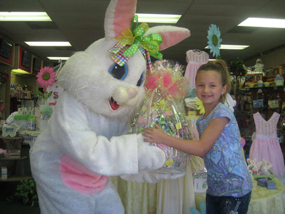 The Easter bunny hands a basket to 8-year-old Gracie Ratcliff at Bab's  on Tuesday. Customers can have the Easter bunny deliver gift baskets ordered at Bab's through Friday. Heather Nolan/The Enterprise