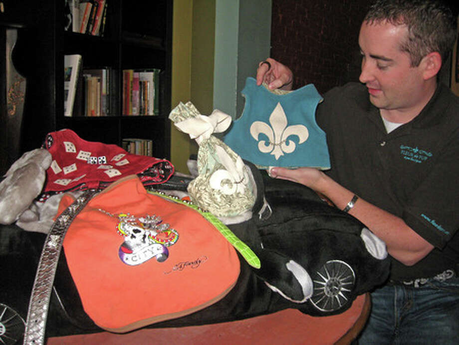 Greg Wright, an owner of the online pet boutique Fleur de Pup, shows off some of the merchandise for sale on his Web site. Heather Nolan/The Enterprise