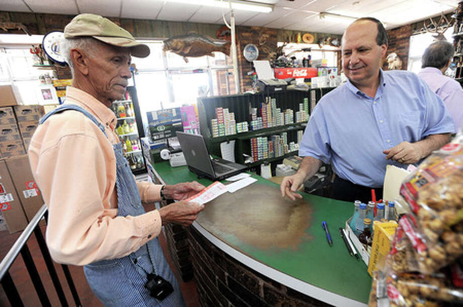 Raymond Evans purchases a scratch off ticket Wednesday from Joe Messina at Debb's Liquor in Beaumont.  Guiseppe Barranco/The Enterprise