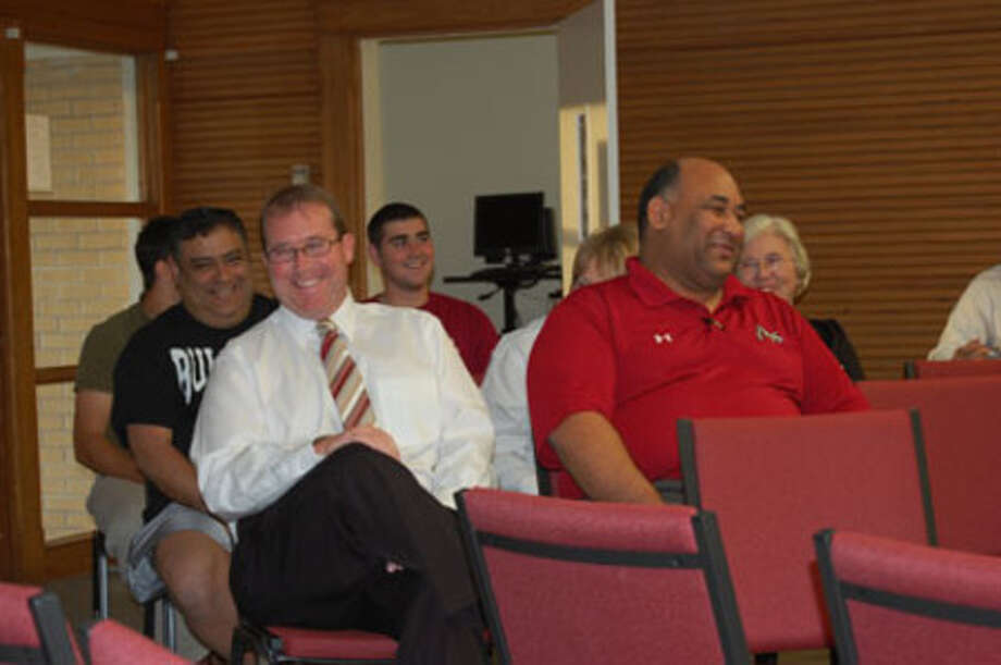 Mike Bickham, left, and Jasper Athletic Director Thomas Brooks, right, share a laugh during Bickham's announcement as the new football coach for the program.