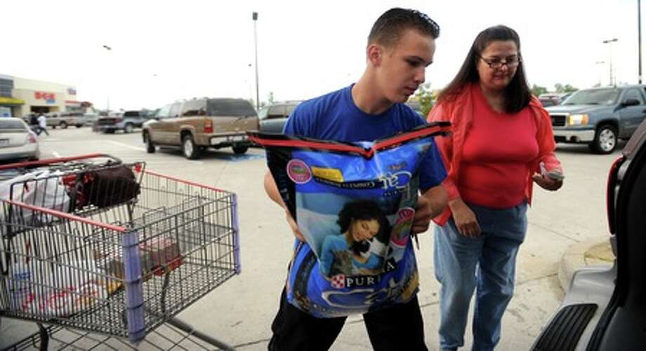 June Gardner and Thomas Savoy load their groceries into their vehicle at H-E-B in Beaumont, Thursday. Tammy McKinley, The Enterprise