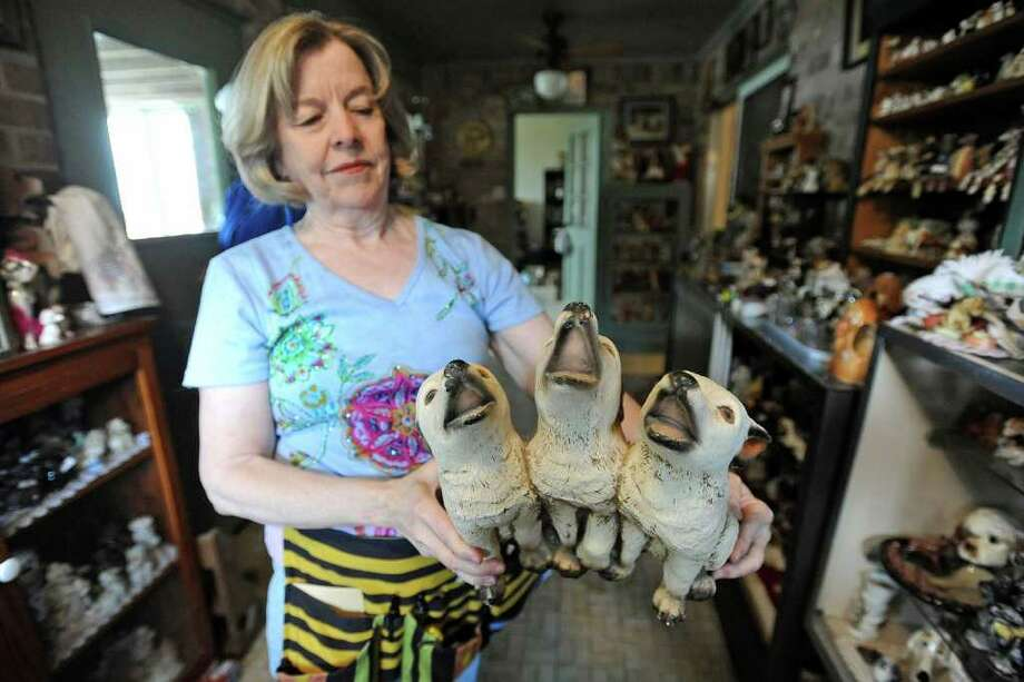 Pat Daleo shows one of the many dog figurines from the estate of Maurine Gray to be sold during an upcoming estate sale. Among the Gray collection are more than 1,000 dog figurines.  Valentino Mauricio/The Enterprise