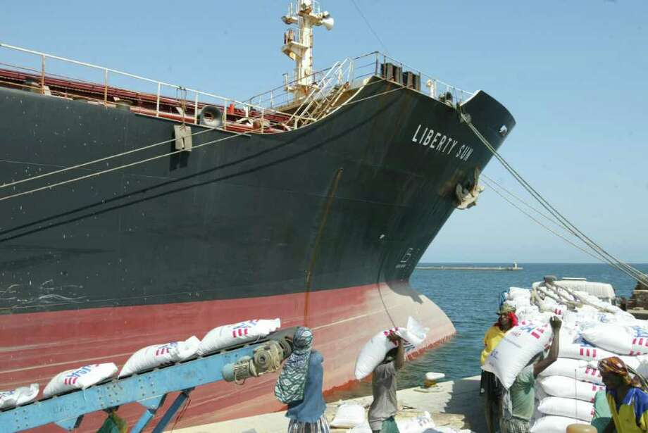 In this photo taken Nov. 5, 2004, workers unload food aid from the MV Liberty Sun at Eritrea's main Red Sea port, Massawa. Somali pirates attacked and damaged an American ship carrying humanitarian aid Tuesday, April 14, 2009 but the ship and crew were safe under Navy escort, the military and shipping company said. (AP Photo/Karel Prinsloo) / AP