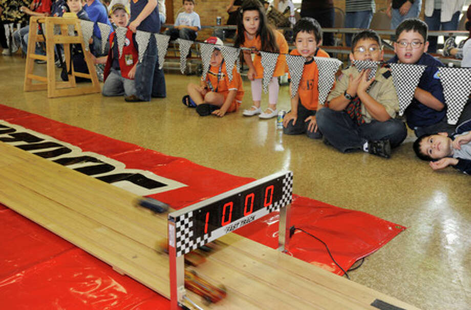 Cub Scouts, Boy Scouts, and their families enjoy the speed and action of the Pinewood Derby at St. Andrews Presbyterian Church on Saturday.  Valentino Mauricio/The Enterprise