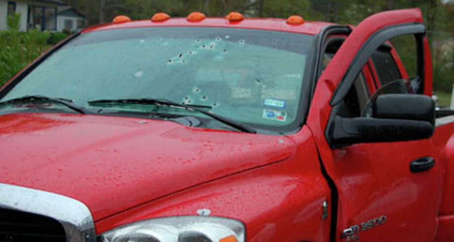 A red dually truck is parked at the Jasper Police Station as evidence of the shooting at the Timbers Apartments