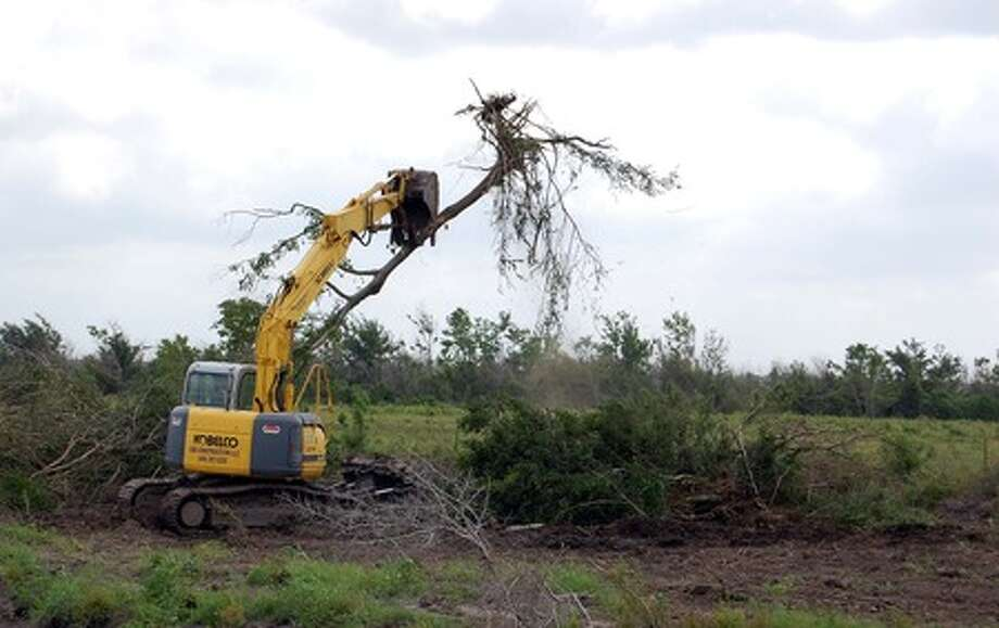 A Chambers County rancher clears debris from his land hit by Hurricane Ike's storm surge. Federal fundings for debris removal decreased last week, and some remaining debris may not be removed.
