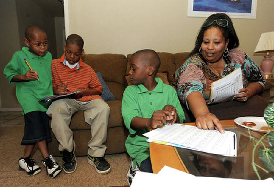 Lark Turner helps (from left) Dray Turner, Reealdo Turner and Javonta Turner work on homework after school on Thursday. A single mother, Turner has cared for 10 adopted children, several of which are special needs. Guiseppe Barranco/The Enterprise