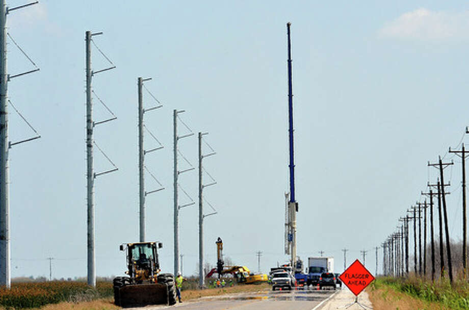 Workers erect power lines along Texas 124 on Thursday. Guiseppe Barranco/The Enterprise