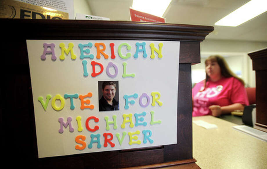 Bank teller, Kelli Payne works behind a counter that has several signs supporting American Idol contestant, Michael Sarver at the First Bank and Trust in Jasper, Friday. Tammy McKinley, The Enterprise