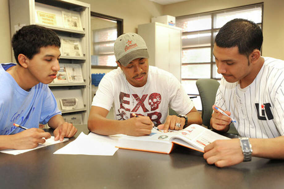 Lamar business student and tutor, Joshua Cratic, center, helps LIT student, Francisco Lopez, left, and Emanuel Lugo, right, with quadratic equations during a recent math tutoring session at the LIT learning and computer lab.  Valentino Mauricio/The Enterprise