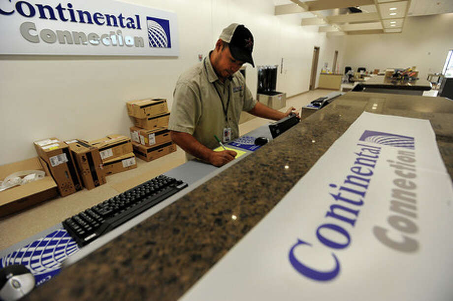 Mark Ramirez installs computers at the Continental ticket center on Thursday. The new terminal at the Southeast Texas Regional Airport is slated to be open for operations on Monday. Guiseppe Barranco/The Enterprise