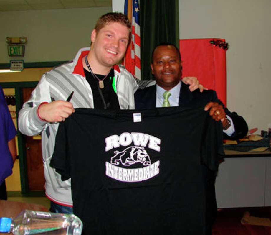 Courtesy photo  Michael Sarver visited Rowe Campus Monday, April 27 to inspire the students to do well on the TAKS test. Pictured above, Sarver receives a Rowe T-shirt from Rowe Principal Victor Williams.