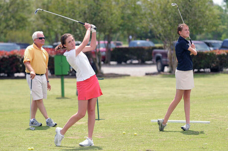 Kelly High School golf coach Don Keen, left, works with Michala Bradley, right, and Kelly Bellard in preparation for the TAPPS Class 5A state golf tournament.  Valentino Mauricio/The Enterprise
