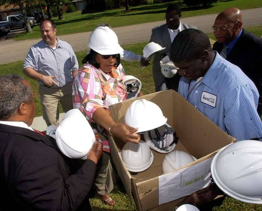 Sybil Comeaux, center, passes out hardhats to the officials invited to the  Amelia Elementary School ground breaking.   BISD broke ground Tuesday on the first of the nine elementary schools it plans to build with the bond money. Dave Ryan/The Enterprise