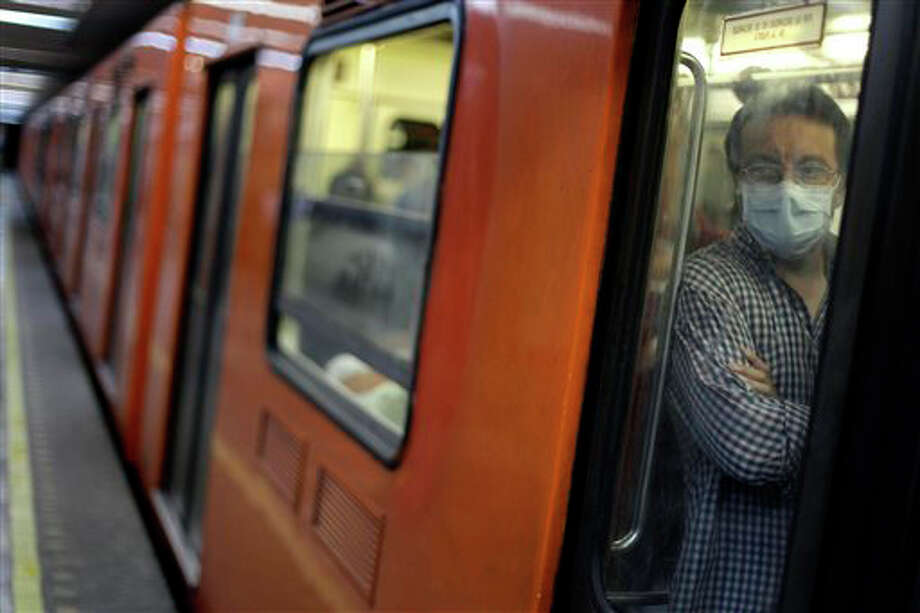 A man wearing a face mask stands inside a subway train in Mexico City, Monday, April 27, 2009.  A fatal strain of swine flu has been detected in Mexico while the virus has been confirmed or suspected in at least a half-dozen other countries. (AP Photo/Rodrigo Abd) / AP