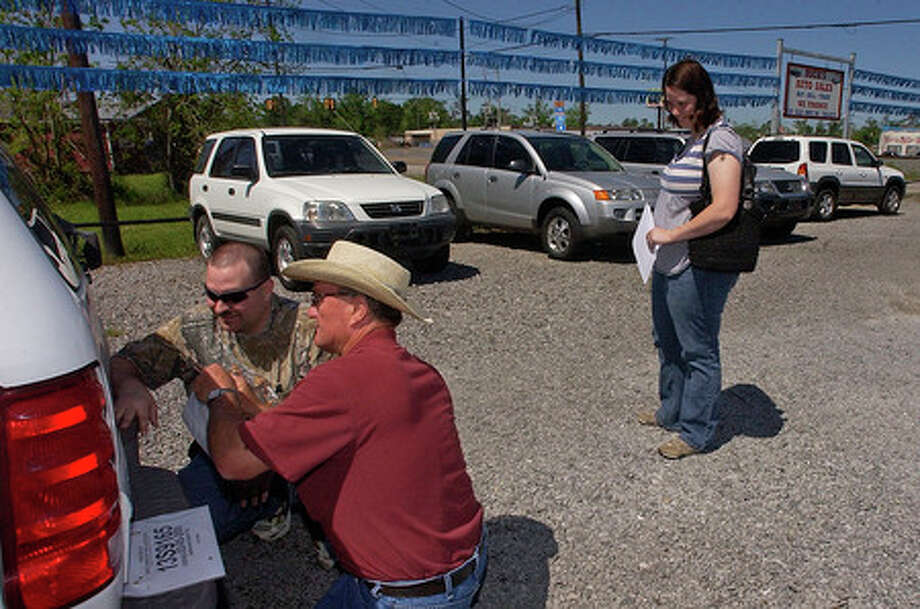 Local Vidor cars salesman Rick Wilson, middle, helps Joshua Opferkuch, left, put the new temporary tags for his new vehicle on, before driving off the lot with his wife Jan. Dave Ryan/The Enterprise