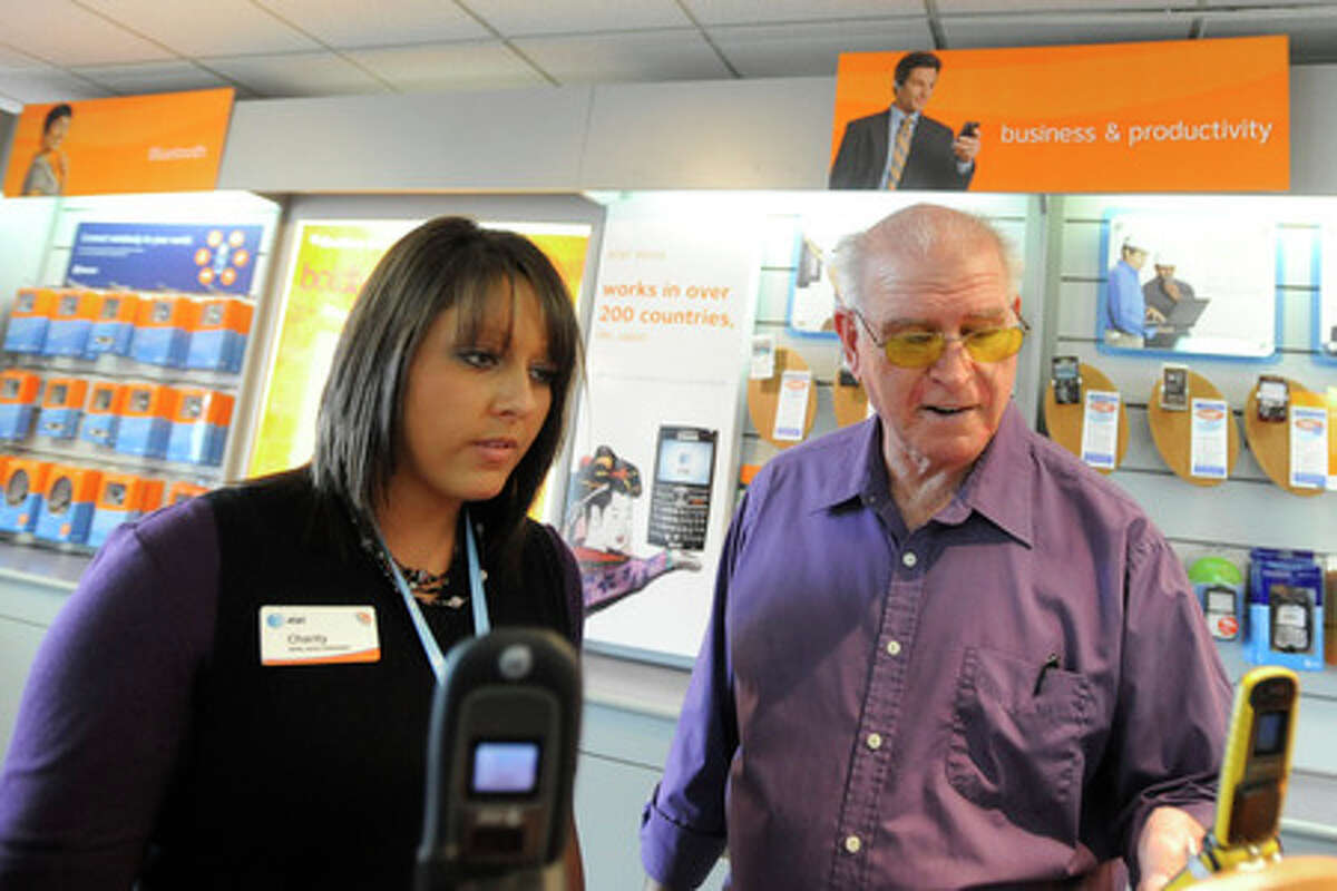 AT&T retail sales consultant, Charity Callan, left, helps Kirbyville resident Billy Hall select a cell phone at the AT&T store on Dowlen Rd. Valentino Mauricio/The Enterprise