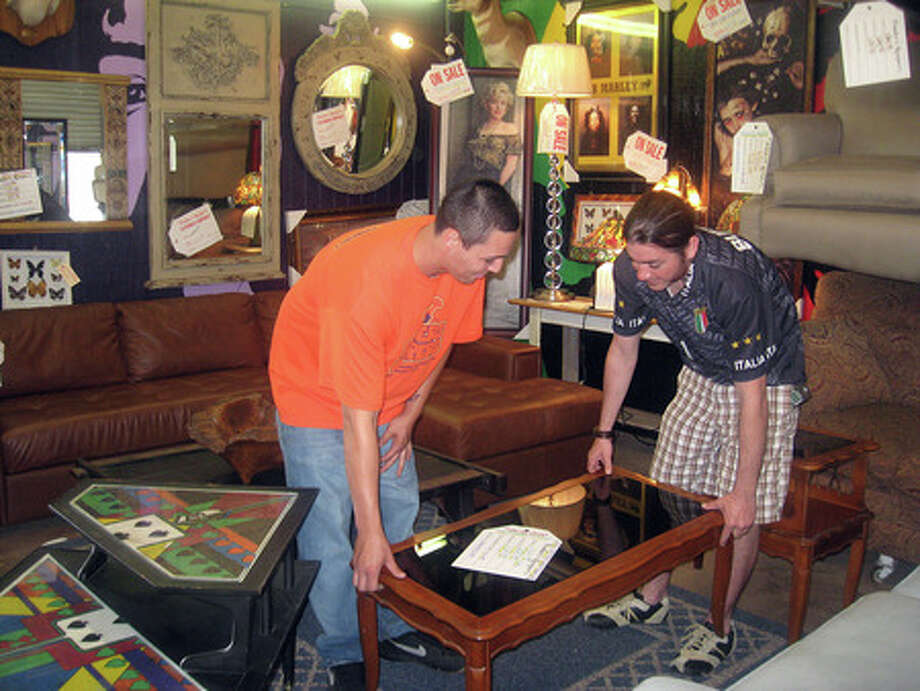 Store associate Cameron Zamora, left, and store owner Eric Marroquin Jr. move a coffee table at Finder?s Keeper?s on Eastex Freeway. The consignment store has been open since 2004. Heather Nolan/The Enterprise