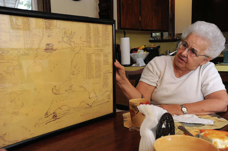 Ruth Sanford holds her 1885 map of Galveston Bay in her Woodville home on Thursday.