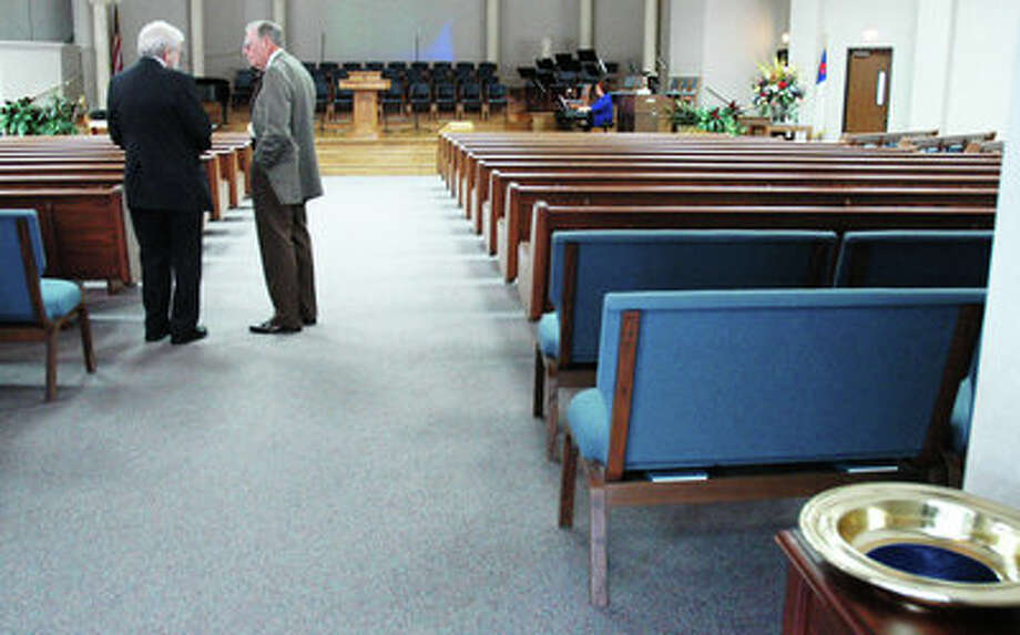 An empty collection plate sits in the sanctuary of Westgate Memorial Baptist Church while Beaumont residents Grover Dowden, 81, right, and Joe Jones, 81, talk. Lluvia Rueda/The Enterprise