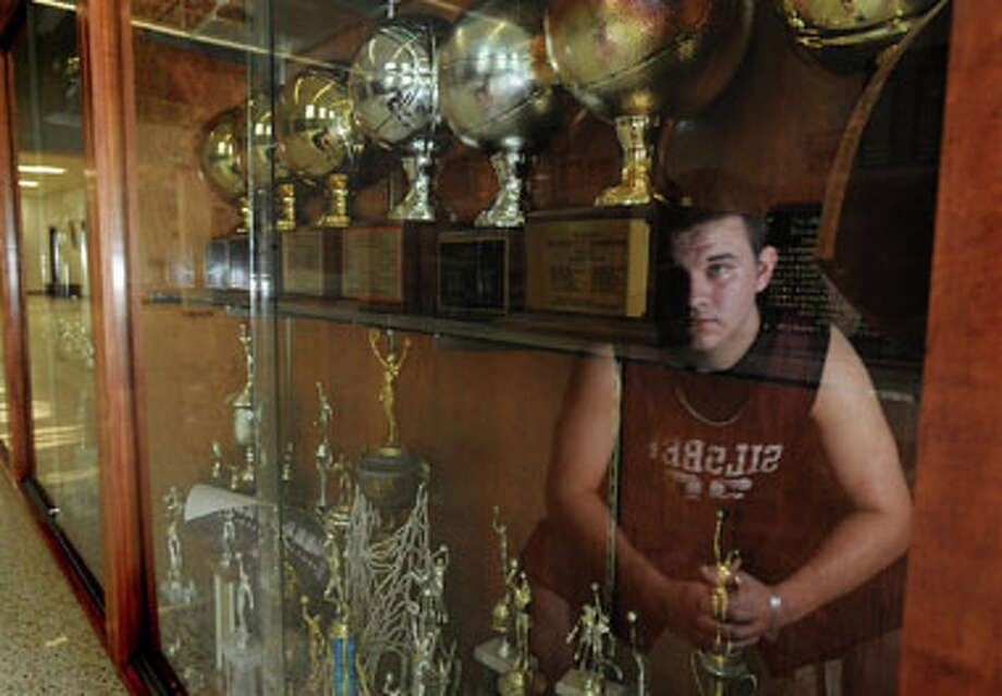 Silsbee's Brady Byars poses next to the school's trophy case containing several awards obtained by the basketball teams. Guiseppe Barranco/The Enterprise