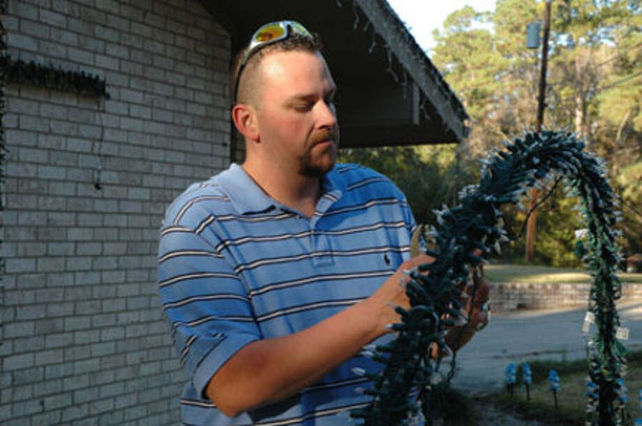 Daniel Havard puts the finishing touches on a ring of lights in his front yard. Havard has put music to his Christmas lighting display at 601 Live Oak and invites the public to come and enjoy the spirit of the Christmas season.