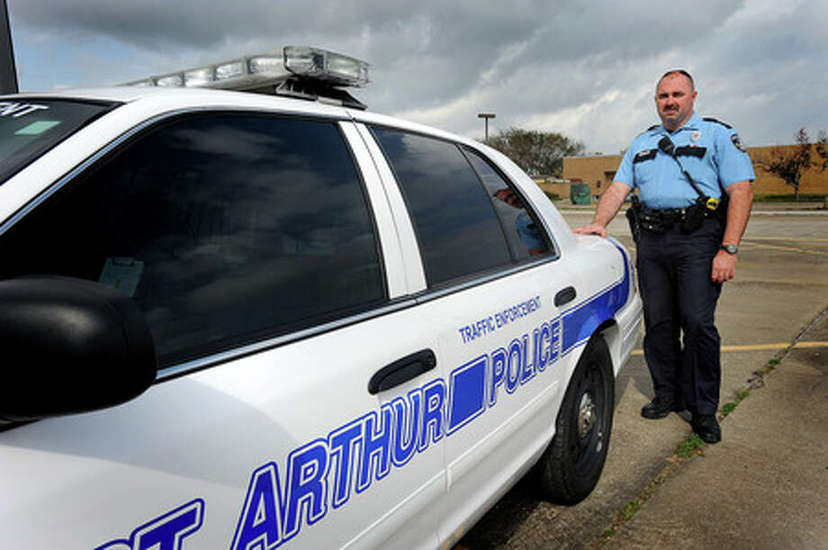 FILE - Port Arthur Police Officer Chuck Cobb places his hand on a police car where the city's new license plate readers will be installed. Council authorized, Tuesday, for the purchase of two units that will rapidly scan license plates for outstanding warrants. Tuesday, January 27, 2009