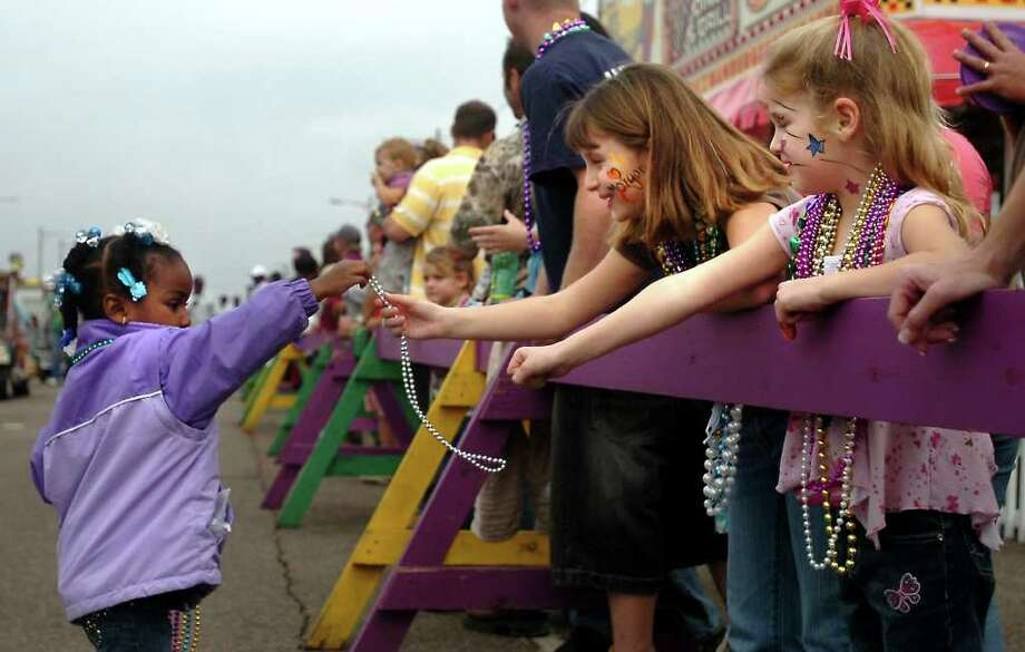 Johna Mayon hands beads to Morgan and Harlee Brown during the Munchkin Parade during Mardi Gras celebrations in Port Arthur, TX, Sunday, February 3, 2008. Beaumont Enterprise, Tammy McKinley
