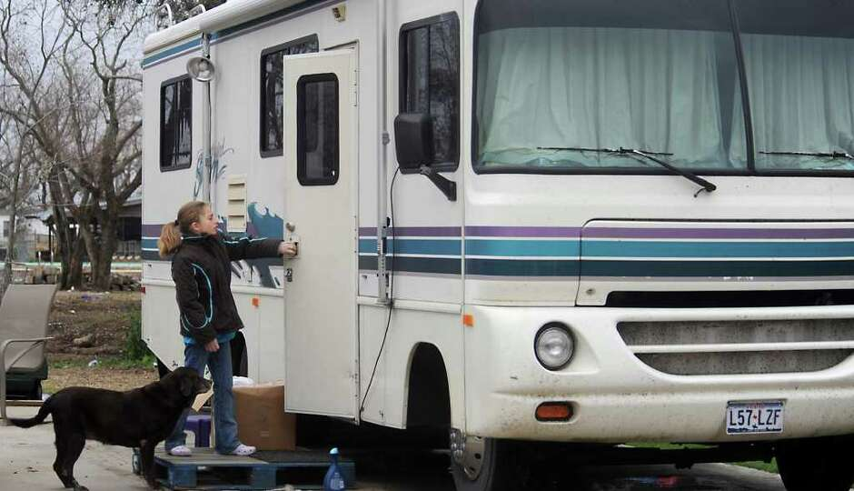 Olivia Saunders goes into her father's RV in Sabine Pass, Friday. Hurricane Ike wiped out the Saunde
