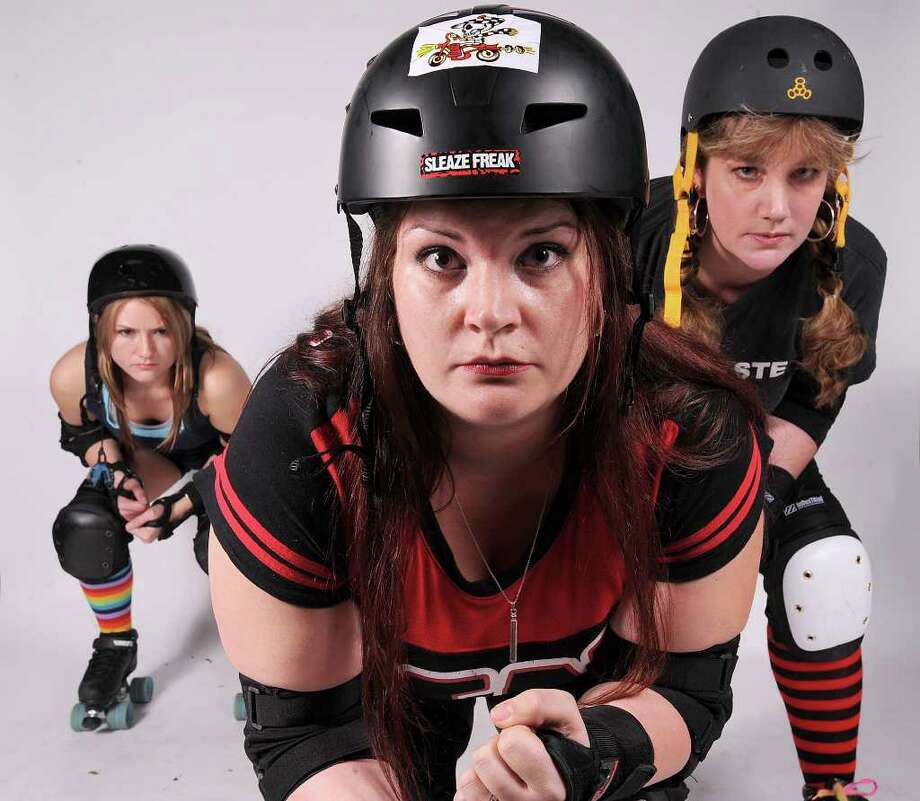 Robbi Murphy, front, Merry Dawn Bruce, left, and Dawn Henson of the Spindletop Rollergirls. Guiseppe Barranco/The Enterprise
