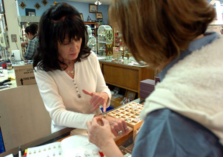 The Joy Shop owner Joy Taylor shows bracelets to her customer of 25 years Leslie Schroder at the store Monday afternoon. Local retailers such as The Joy Shop recorded strong sales through the holidays. Pete Churton/The Enterprise