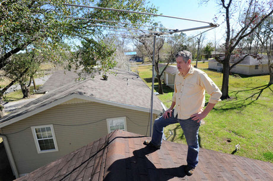 Beaumont resident, Thomas Comte, stands on his rooftop next to the antenna that he will soon need to replace once the digital television conversion takes place.  Valentino Mauricio/The Enterprise