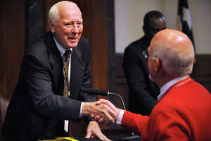 In a sign of congratulations, Hal Ross shakes Waymon Hallmark's hand at the end of Hallmark's final commissioners court meeting on Monday, December 22, 2008. Hallmark retired after 14 years of service. Guiseppe Barranco/The Enterprise