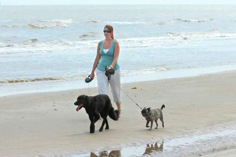 Leslie Bailey of Orange enjoys a stroll at McFaddin Beach with her two dogs Stella, left, and Katie. An advisory was issued for McFaddin and Sea Rim beaches because of high levels of bacteria detectedin the water. Valentino Mauricio/The Enterprise
