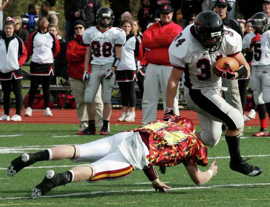 Fairfield Warde's David Wolff breaks a tackle from St. Joseph player Tyler Matakevich during Saturday's game at St. Joseph's in Trumble. Photo: David Ames / Connecticut Post