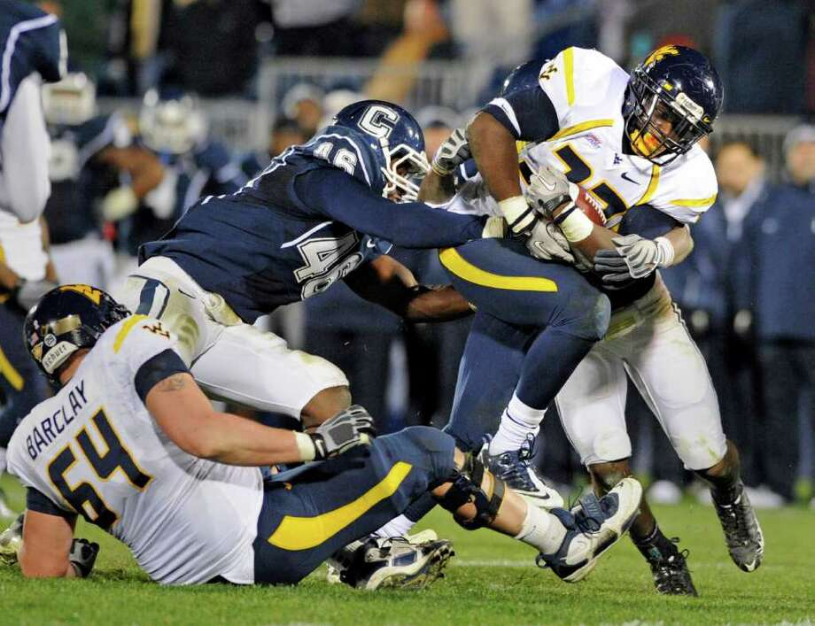 West Virginia's Ryan Clarke is tackled by Connecticut's Sio Moore, left, and Jerome Junior, background, during overtime in Connecticut's 16-13 victory in their NCAA football game in East Hartford, Conn., on Friday, Oct. 29, 2010. Clarke fumbled on the play and the ball was recovered by Connecticut, setting up their game winning drive. (AP Photo/Fred Beckham) Photo: AP