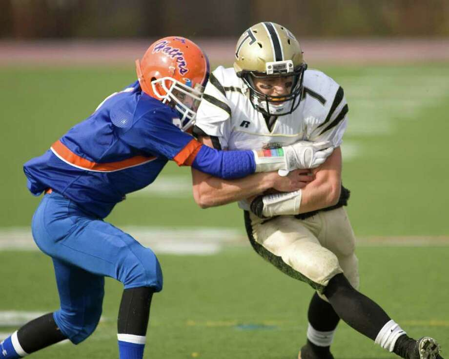 Trumbull's Ian Milne, right, gains yardage before being stopped by Danbury's Anthony Nejame Saturday, Oct. 30, 2010, at Danbury High School. Photo: Barry Horn / The News-Times Freelance