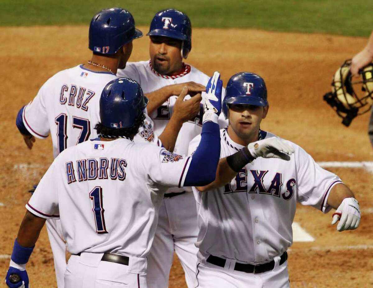 Texas Rangers' Mitch Moreland, right, is congratulated by his teammate after hitting a three-run home run during the second inning of Game 3 of baseball's World Series San Francisco Giants Saturday, Oct. 30, 2010, in Arlington, Texas. (AP Photo/Mark Humphrey)