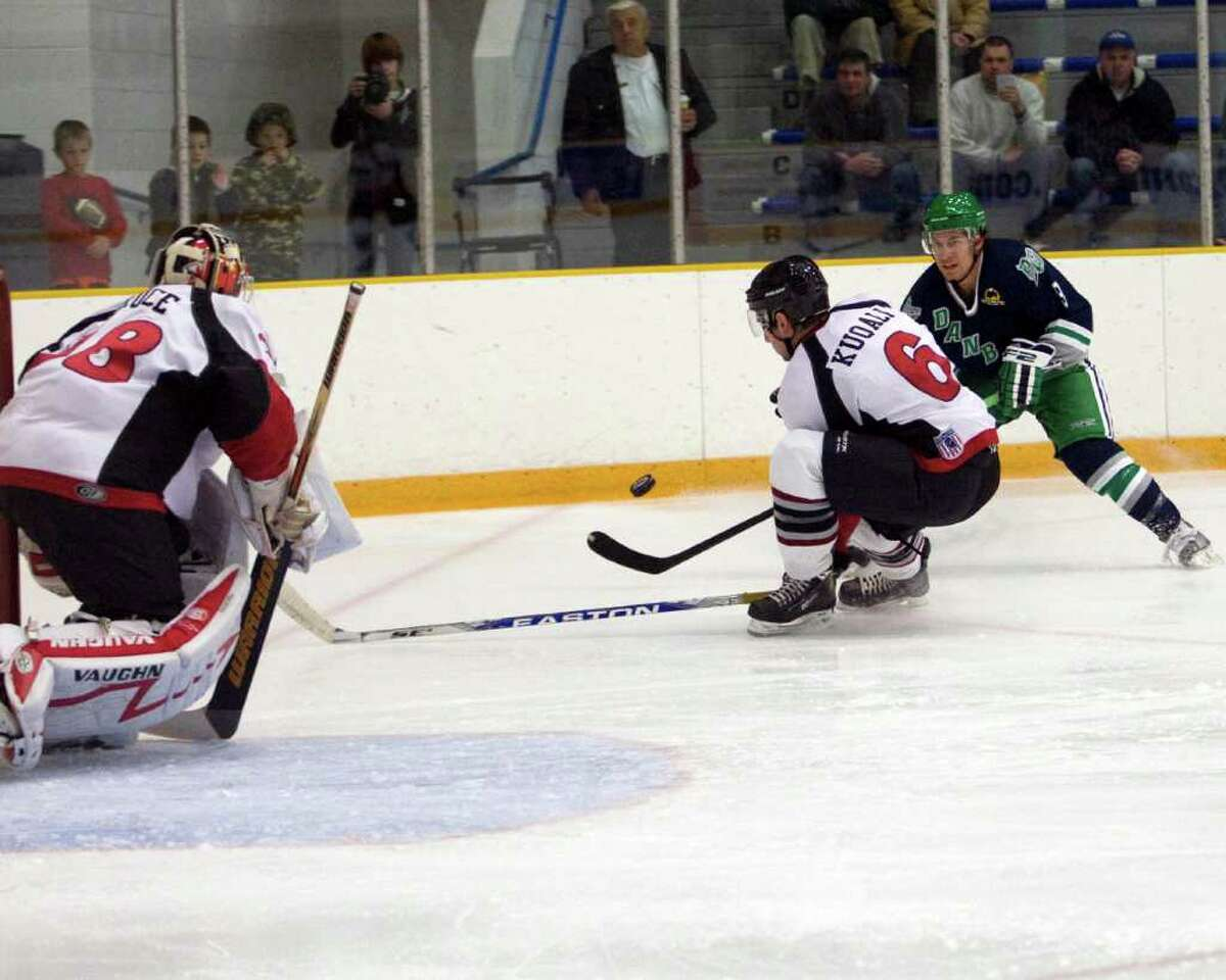 The Whalers' J.R. Bria, right, fires a shot past New York defenseman Nick Kuqali while goalie Kevin Druce waits to make a save Saturday night at the Danbury Arena.