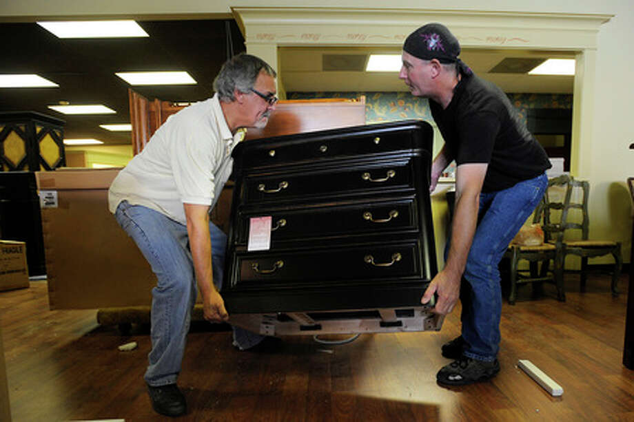 Ebb Moore, owner of Parlours in Orange, and employee, David Franklin, ready new furniture for a reopening after Thanksgiving.  Valentino Mauricio/The Enterprise